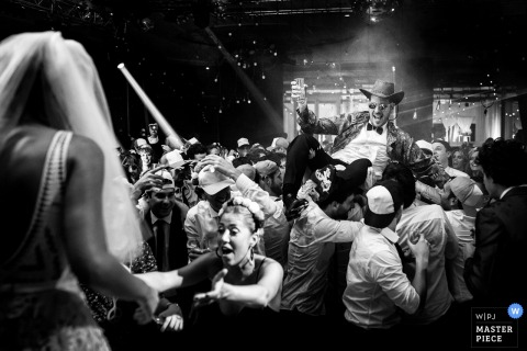 Santa Fe wedding photographer captured this black and white image of a groom crowd surfing on the dance floor while his bride watches nearby
