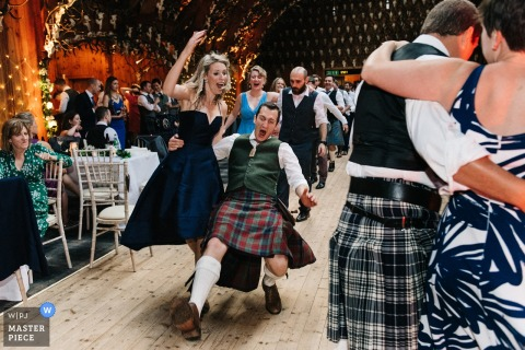 Scotland wedding photographer captured this image of the bridal party dancing on a wooden dance floor with the men in traditional scottish dress