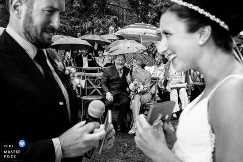 La mariée et le marié se sourient tandis que leurs parents observent en arrière-plan cette photo réalisée par un photographe de mariage de Lake Tahoe