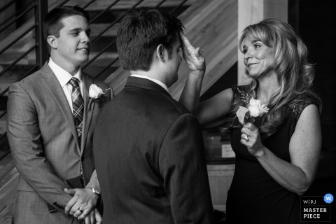 Missioula wedding photographer captured this black and white image of the mother of the groom playfully fixing his hair before the ceremony