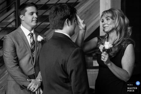 Fotograf ślubny Missioula uchwycił ten czarno-biały obraz matki pana młodego żartobliwie układając włosy przed ceremonią