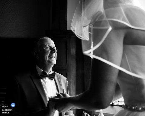 Le photographe de mariage londonien a créé cette image en noir et blanc du père de la mariée lui souriant avec amour avant de marcher dans l'allée
