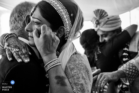 A bride wipes a tear from her eye as she embraces her father in this black and white photo as captured by Madrid wedding photographer