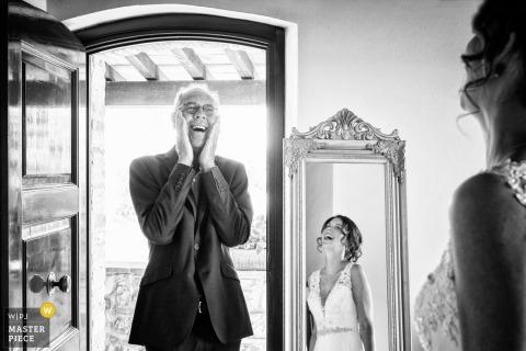 Le photographe de mariage d'Arezzo a capturé cette photo en noir et blanc de l'expression charmante du père des épouses lorsqu'il voit sa fille dans sa robe de mariée pour la première fois. On peut la voir rire dans le miroir en face d'elle dans la chambre