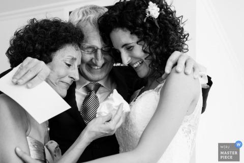 Le photographe de mariage de Barcelone a capturé cette photo en noir et blanc d'une jeune mariée souriante embrassant ses deux parents dans l'attente de la cérémonie
