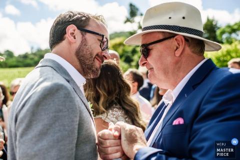 Libson Hochzeitsfotograf nahm dieses Bild eines Bräutigams auf, der von seinem Vater nach der Hochzeitszeremonie beglückwünscht wurde