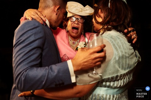Florence wedding photographer captured this image of a bride and groom being captured in a big hug by his mother after they exchanged their vows