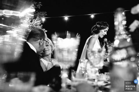 Portofino wedding photographer captured this black and white image of a bride giving her speech while her parents smile nearby