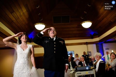 Le photographe de mariage de Burlington a capturé cette mariée et son père vêtu d'uniforme en train de saluer avant la cérémonie