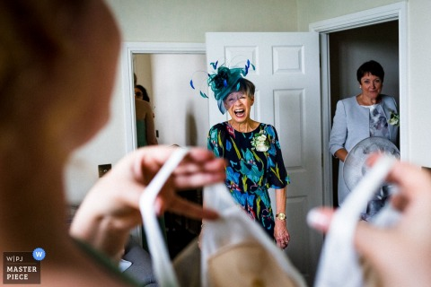 Hertfordshire wedding photographer captured this image of the brides mother in a blue fascinator hat seeing the dress for the first time