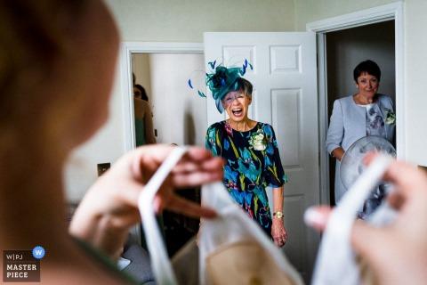 Le photographe de mariage du Hertfordshire a capturé cette image de la mère de la mariée dans un chapeau bleu fascinateur voyant la robe pour la première fois