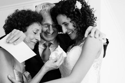 Barcelone, Espagne La photographe de mariage Marga Serrano Martí a photographié cette image de la mariée partageant un câlin et un rire avec ses parents avant la cérémonie.