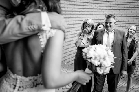 Overijssel, photographe de mariage néerlandaise, Indra Simons, utilise son style de reportage pour documenter les parents de la mariée qui réagit en la voyant.