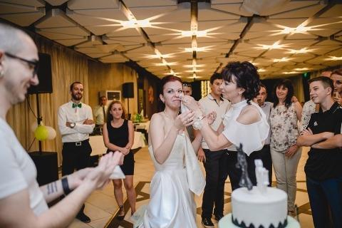Sofia, Bulgarie Photographe de mariage, Linda Alexandriyska a documenté cette épouse qui se faisait aider par maman après le démantèlement du gâteau ... sous le regard du marié.