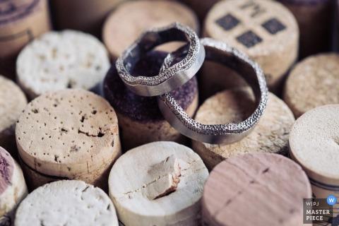 Der Berner Hochzeitsfotograf hat diese Detailaufnahme der Eheringe der Paare aufgenommen, die auf Weinflaschenkorken ruhen