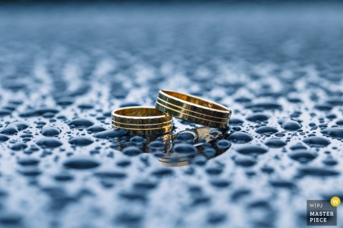 Lower Silesian wedding photographer captured this detail shot of the bride and grooms wedding bands resting on a surface covered in water droplets