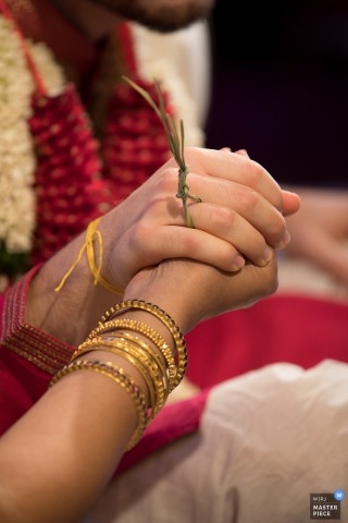 San Francisco wedding photographer captured this photo of a gold bangle adorned bride and groom clasping hands while holding a sprig of pine