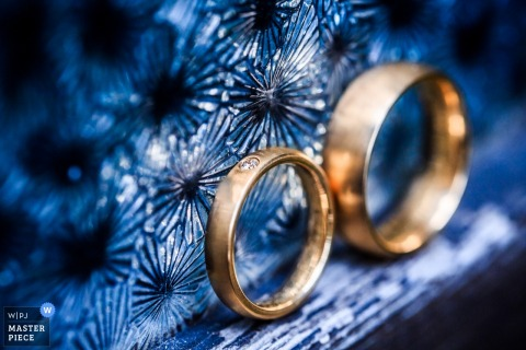 Baden-Wurttemberg wedding photographer captured this beautiful detail photo of two gold bands resting against a royal blue glass wall