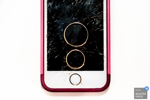 Santa Fe wedding photographer captured this photo of wedding bands resting on the cracked and broken screen of an iphone