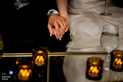 This detail shot of a bride and groom holding hands next to a candle filled table was captured by a Boston wedding photographer