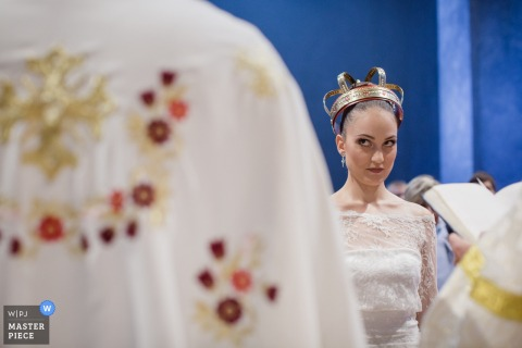 The bride wears a crown on her head as she looks over at the priest in this photo by a Lombardy wedding photographer.