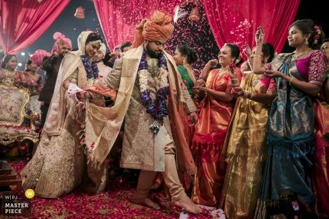 Het bruidsfeest gooit roze bloemblaadjes naar de bruid en bruidegom als ze de ceremonie verlaten in deze foto door een trouwfotograaf uit Montpellier.