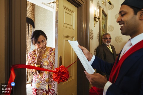 The bride is blocked from entering room by a red ribbon where the groom reads a letter in this photo taken by a London, England wedding reportage photographer.