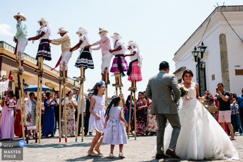 The bride and groom stand in a square as a group of people wearing traditional clothing walk on stilts behind them in this photo by a Oaxaca, Mexico wedding photographer.