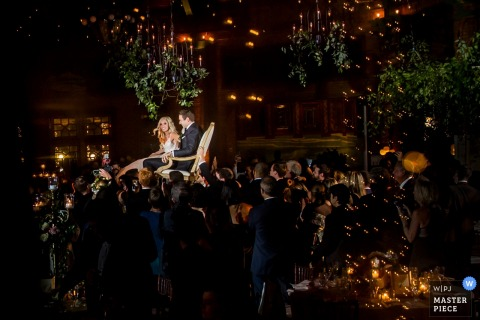 The guests lift the bride and groom up in their chairs and carry them in this photo by a Chicago, IL wedding photographer.