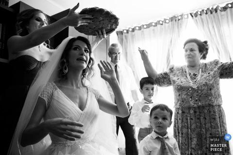 Foto en blanco y negro de la familia de la novia realizando una ceremonia cultural antes de la boda de un fotógrafo de bodas en Bucarest, Rumania.