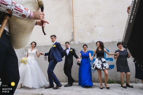Photo of the bride, groom, and guests dancing in a row as a man plays an instrument by a Sofia, Bulgaria wedding photographer.