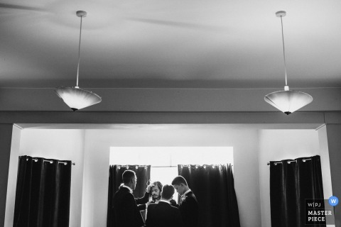 A Derbyshire, East Midlands wedding picture of some guests gathered around an open window in the center of the room while there are two large hanging lights in view