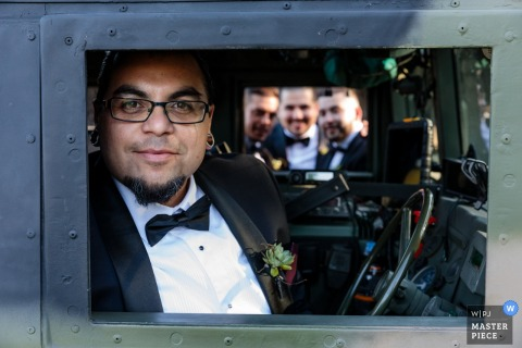 The groom looks out the window of an armored vehicle with his groomsmen are visible on the other side in this portrait by a Melbourne, Australia wedding photographer.