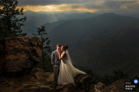 The bride and groom stand on a cliff with mountains behind them in this photo by a Boulder, CO wedding photographer.