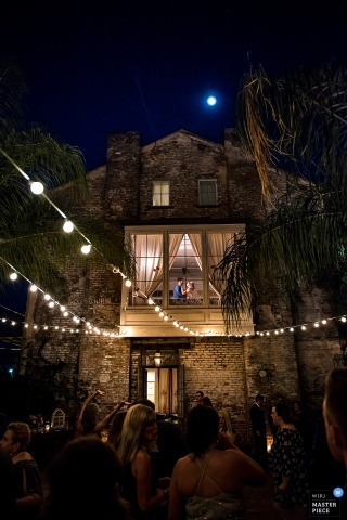 The bride and groom can be seen through a window in the upper floor of a stone house as guests celebrate below outside in this photo by a Boulder, CO wedding photographer.