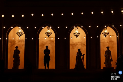 The bride and groom stand silhouetted with statues in the entryway of a building lit up at night in this photo by a San Diego, CA wedding photographer.
