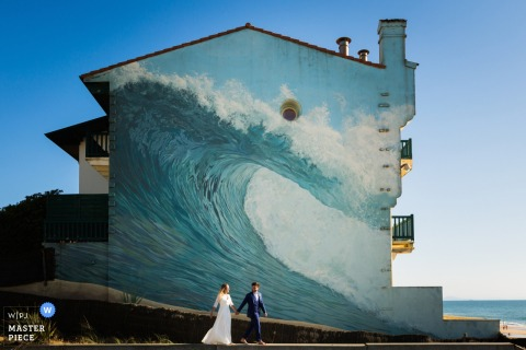 Photo of the bride and groom walking past a building with a large ocean wave painted on it by a Miami, FL wedding photographer.