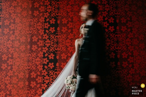 Portrait of the bride and groom against a detailed, red wallpaper by a Lower Saxony, Germany wedding photographer.