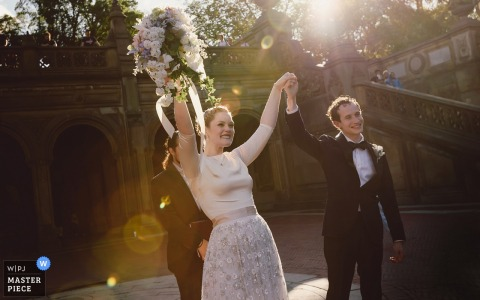 The bride and groom hold hands and raise their arms as they are surrounded by sunlight in this photo by a Manhattan, NY wedding photographer.