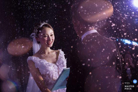 The bride and groom say their vows during the ceremony as lights flare around them in this photo by a Chongqing, China wedding photographer.