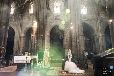 De bruid en bruidegom staan voor de priester in een grote, stenen kathedraal terwijl de zon door de ramen schijnt in deze foto van een trouwfotograaf uit Montpellier.