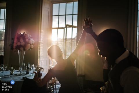 Een man en een vrouw houden hun handen samen in de lucht aangezien het licht door het venster achter hen op deze foto door een de huwelijksreportagefotograaf van Londen, Engeland schijnt.
