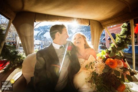 Die Braut und der Bräutigam lachen, als sie auf dem Foto eines Hochzeitsfotografen aus New Jersey hinten in einem Wagen sitzen.
