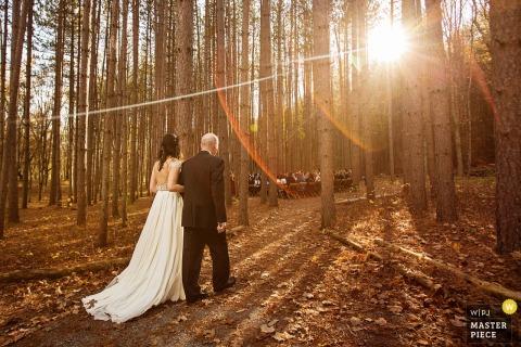 Die Braut geht Arm in Arm mit ihrem Vater durch den Wald in Richtung der Zeremonie, während die Sonne durch die Bäume auf diesem Foto eines Hochzeitsfotografen aus New Jersey scheint.