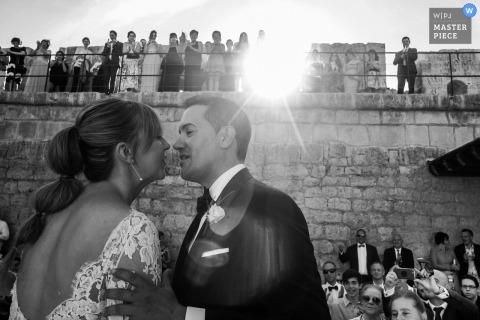 Zwart-witte foto van de bruidegom en de bruid ongeveer tijdens de ontvangst te kussen aangezien de gasten door een huwelijksfotograaf van Leon letten op.