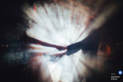 Photo of the bride and groom holding hands shrouded by fog and light by a Porto, Portugal wedding photographer.