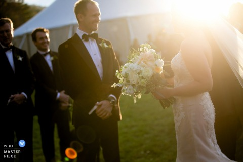 Photo of the bride meeting the groom at the altar with her face blocked by the sunlight by a Knoxville, TN wedding photographer.