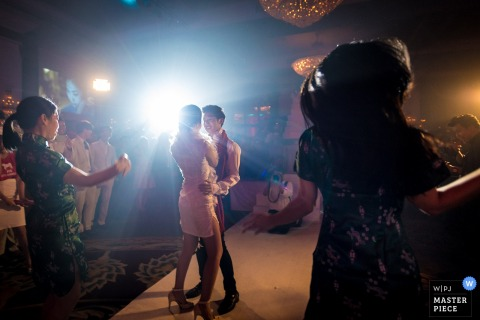 Photo of the bride and groom dancing on the dance floor as a light shines behind them by a Bangkok, Thailand wedding photographer.