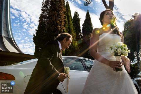 Una foto del día de la boda en Madrid, España de la novia mirando al cielo mientras su padre camina detrás de ella cerca de un automóvil