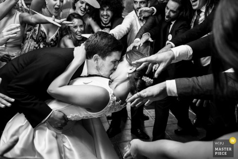 The bride and groom kiss as guests surround them and reach for them in this black and white photo by an Alicante, Valencia wedding photographer.